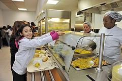 Jeune fille se servant à manger dans une cantine scolaire